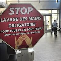 « Stop, lavage des mains obligatoire pour tous et en tout temps; merci de protéger nos patients », est-il écrit sur un panneau dans le hall d'entrée d'un hôpital.