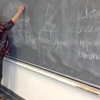 Une enseignante autochtone écrit sur un tableau