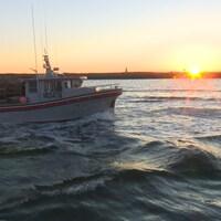 Un bateau se dirige vers la mer au soleil levant.