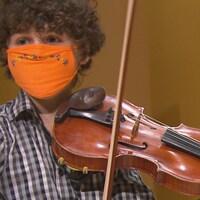 Un jeune homme, avec un masque orange attaché au visage, tient un violon.