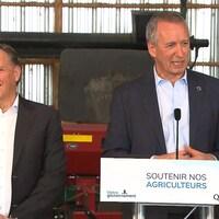 Le ministre André Lamontagne prend la parole, aux côtés du premier ministre François Legault, avec en arrière-plan de l'équipement agricole.