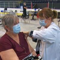 Léna Fortin vaccine une femme sur la glace du Colisée Béton provincial.