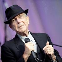 Le chanteur porte un chapeau noir et un complet, micro en main, sur une scène extérieure.