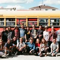 Une vingtaine de planteurs prennent la pose devant le bus jaune des écoliers