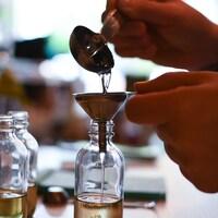 Une cuillère verse un liquide dans un entonnoir déposé sur un contenant en verre pour y faire couler un liquide.