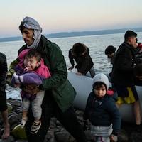 Des parents avec leurs enfants débarquent d'un bateau sur les berges d'un île.