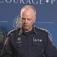 Roger Chaffin, en uniforme devant une affiche avec les logos de la police de Calgary.