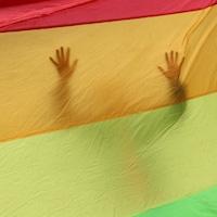 Une silhouette se dessine dans un immense drapeau arc-en-ciel.