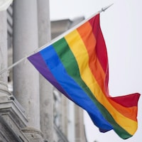 Un drapeau aux couleurs arc-en-ciel est vu accroché à un édifice. Le vent le fait balloter.