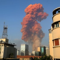Un panache de fumée rouge s'élève dans le ciel.