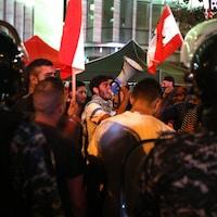 Des gens manifestent devant des policiers antiémeutes.