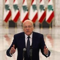 Un homme devant une rangée de drapeaux du Liban.