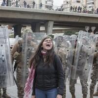 Une femme crie devant une rangée de militaires casqués, armés de matraques et protégés par des boucliers.