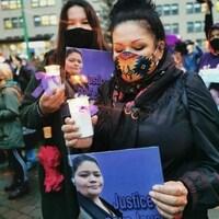 Nicole Awashish porte un masque et tient une affiche avec la photo de Joyce Echaquan.