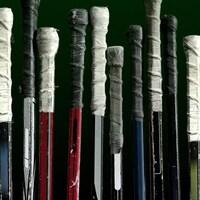 Douze bâtons de hockey alignés un à côté de l'autre.