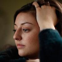La jeune femme est assise, la tête appuyée contre sa main. Elle regarde droit devant elle, comme plongée dans ses pensées.
