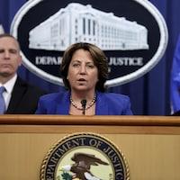 Entourée de deux personnes, Lisa Monaco s'adresse aux reporters devant un drapeau américain et derrière un micro dans la salle de presse du département de la Justice.