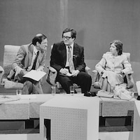 Lise Bissonnette, assise parmi un panel d'hommes.