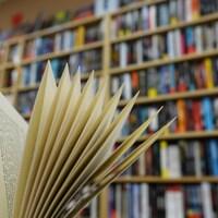 Au premier plan, un livre ouvert devant une bibliothèque bien remplie.