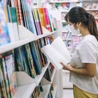 Une femme portant un masque feuillette un livre.