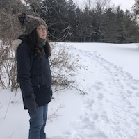 Un femme debout sur un terrain enneigé.