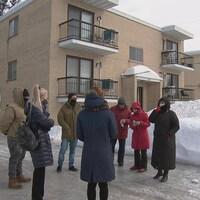 Un groupe de personne discute devant un immeuble à logements