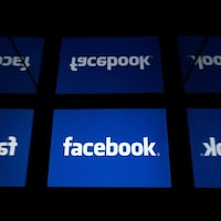 Des écrans arborent le logo blanc et bleu de Facebook.