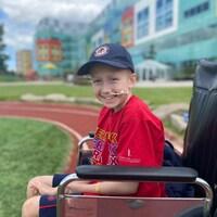 Loic Germaine est dans un fauteuil roulant, devant l'hôpital pour enfants de l'Alberta à Calgary.
