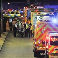 Des polices et du personnel d'urgence transportent une personne blessée lors de l'attaque sur le pont de Londres.