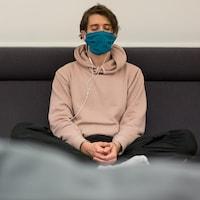 Assis en position tailleur, un intervenant de chez Suicide Action Montréal prend du temps pour se déposer et méditer après un long appel difficile avec une personne en crise.