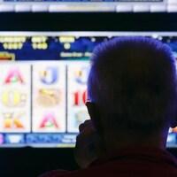 Une homme regarde un terminal de loterie vidéo.