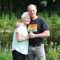 L'homme tient sa mère dans ses bras devant un étang.