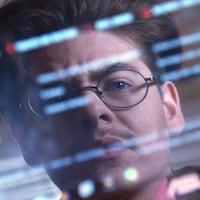 Un homme portant des lunettes regarde son reflet dans un écran d'ordinateur.