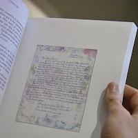 Une main tient le livre, où la page montre un exemple de lettre.