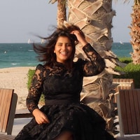 Une femme assise sur un banc à la plage près de l'eau. Elle a les cheveux dans le vent et porte une robe noire.