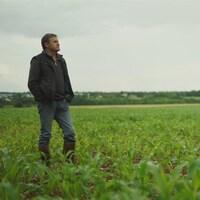L'agriculteur français Paul François debout dans un champs de maïs.