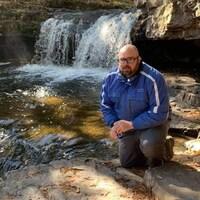 Luc Bélanger près d'une chute, en pleine nature.