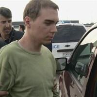 Luka Rocco Magnotta lors d'un transfert, avec des policiers.