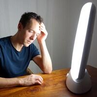 Une photo montrant un homme assis à une table en bois sur laquelle est posée une lampe de luminothérapie.