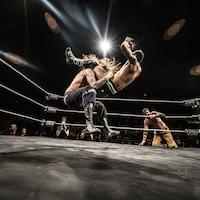 Deux lutteurs dans le ring en plein combat.