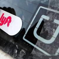Autocollants avec le logo de Lyft et d'Uber sur un pare-brise.