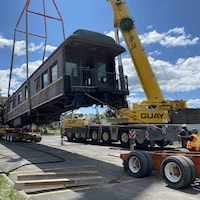 Un wagon de train est soulevé par une grue pour être installé sur un camion.
