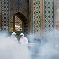 Deux hommes masqués et portant des combinaisons aspergent un produit désinfectant.