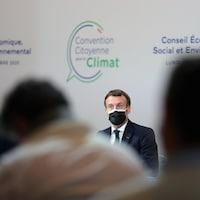 Emmanuel Macron, qui porte un masque, est assis devant une foule lors d'une rencontre publique sur le climat.