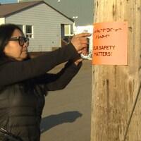"""Madeleine Redfern installe une affiche avec le message """"notre sécurité compte"""" sur un poteau en bois."""