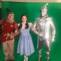 Trois comédiens souriant déguisé en personnage du Magicien d'Oz soit Un épouvantail, Dorothé et l'homme de fer.