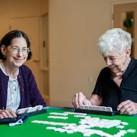 Deux aînés jouent au mah-jong en souriant. Plusieurs tuiles du jeu sont posées sur la table tandis que l'une d'elle prépare ses combinaisons et que l'autre sourit à la caméra.
