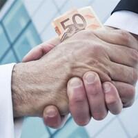 Deux personnes qui s'échangent un billet de 50 $ se donnent la main.