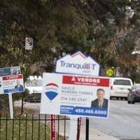Deux pancartes de maison à vendre sur une rue en banlieue de Montréal.