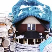 Une maison miniaturisée porte une tuque et un foulard en tenant près d'elle un contenant plein de pièces de monnaie.